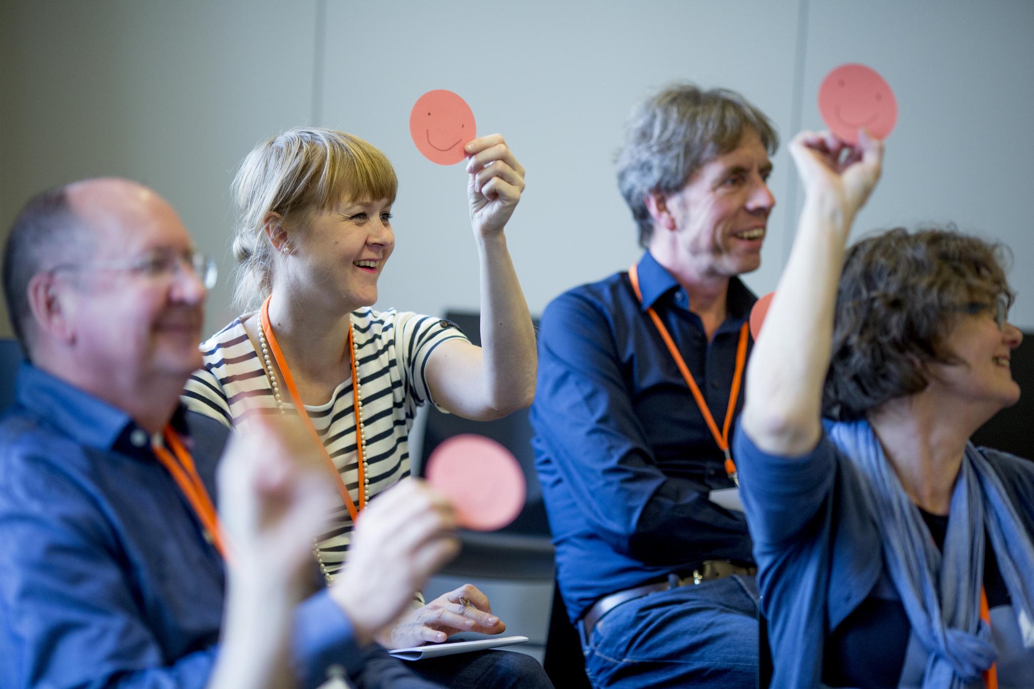 Teilnehmende in einem Workshop halten Zeichen hoch