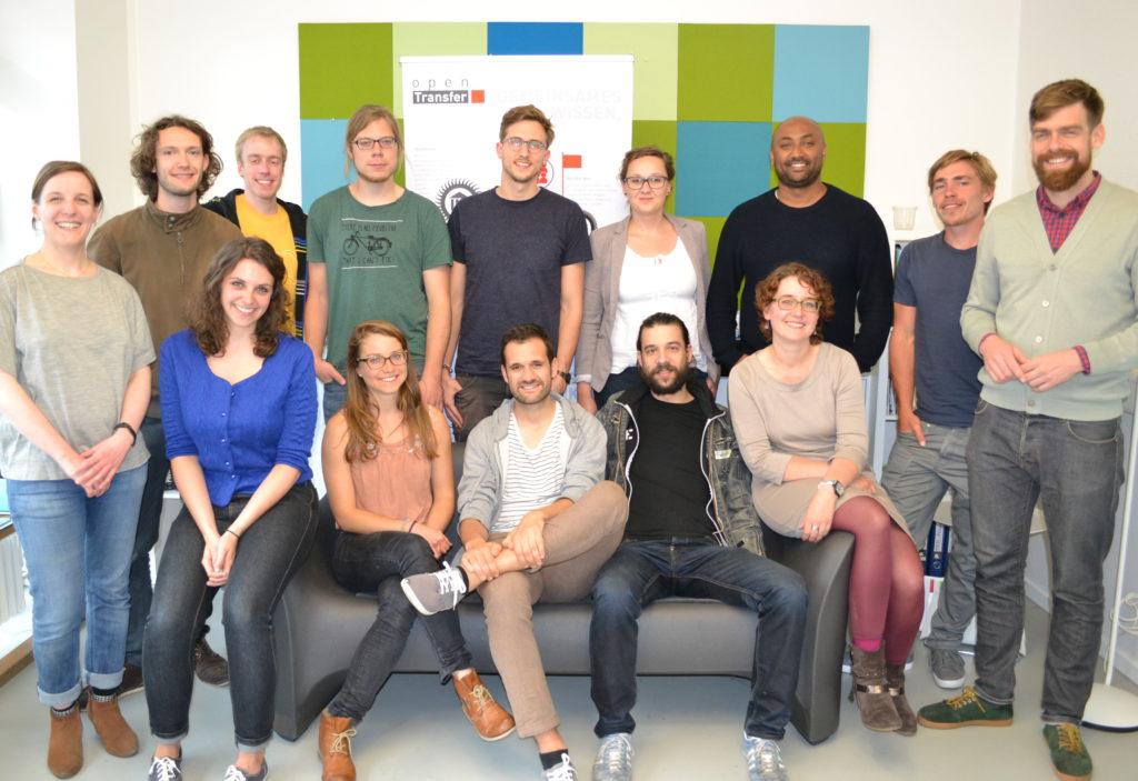 Zehn Männer und Frauen posieren als Gruppe vor einer bunten Wand.