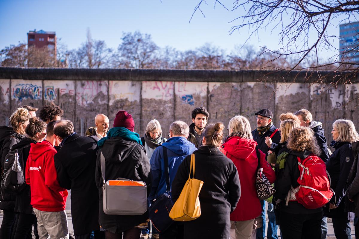 Mehrere Menschen hören einem Mann zu, der vor dem Rest der Berliner Mauer etwas erklärt.