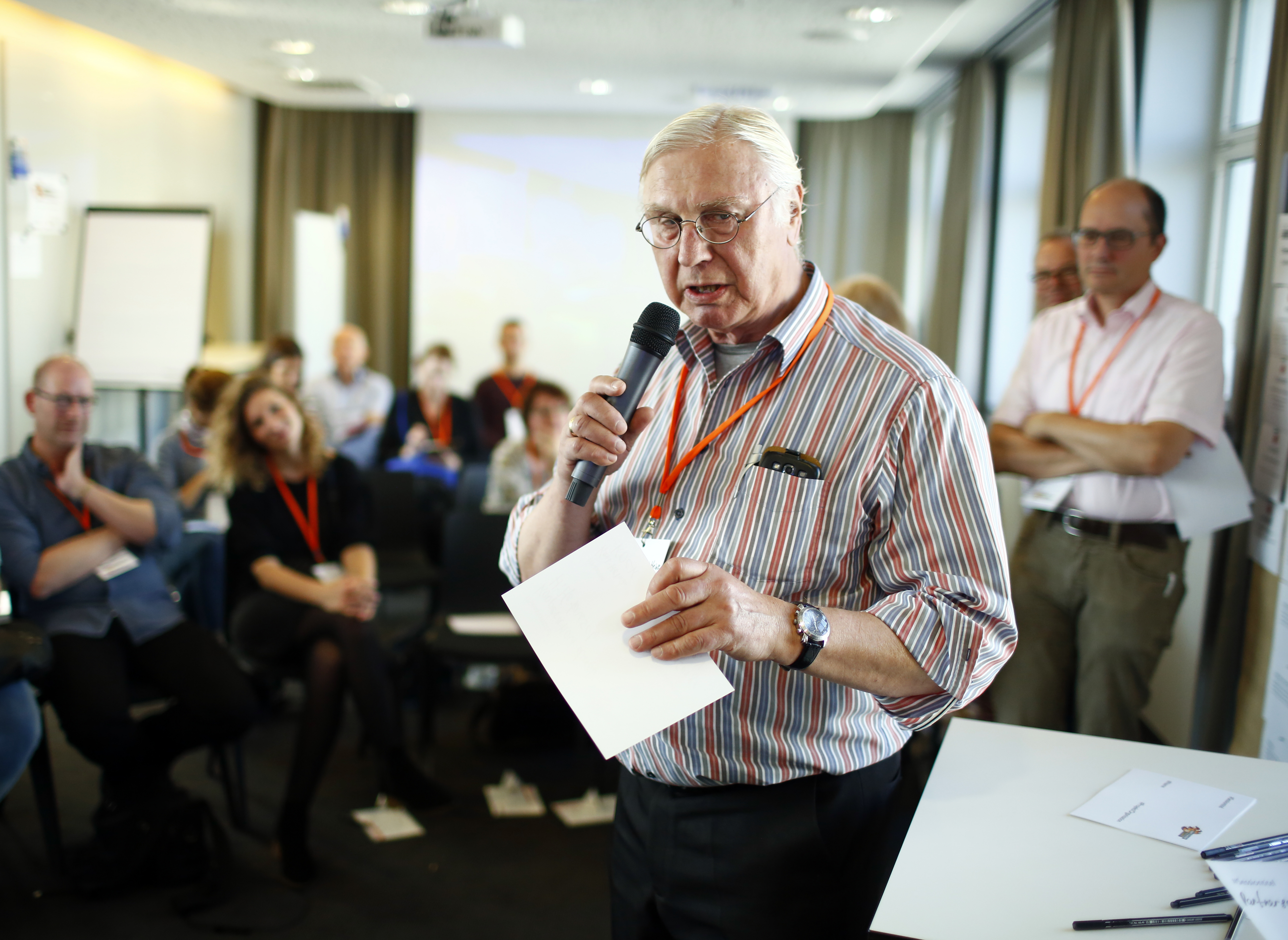 Ein älterer Mann steht mit einem Mikrofon vor einem sitzenden Publikum.
