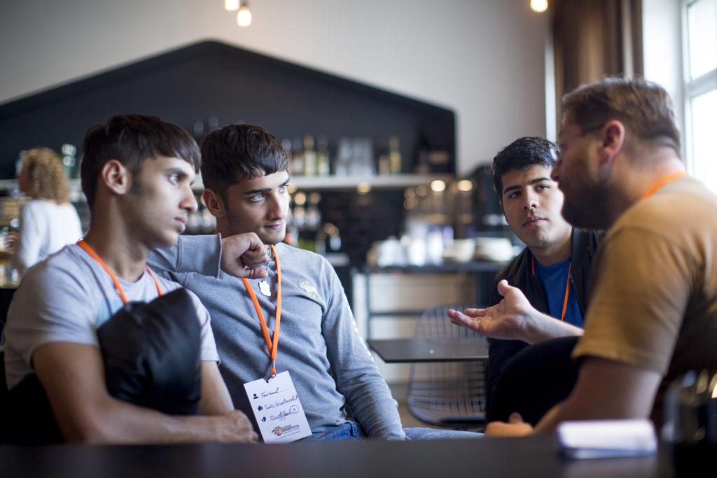 Vier Männer sitzen im Kreis und diskutieren angeregt.