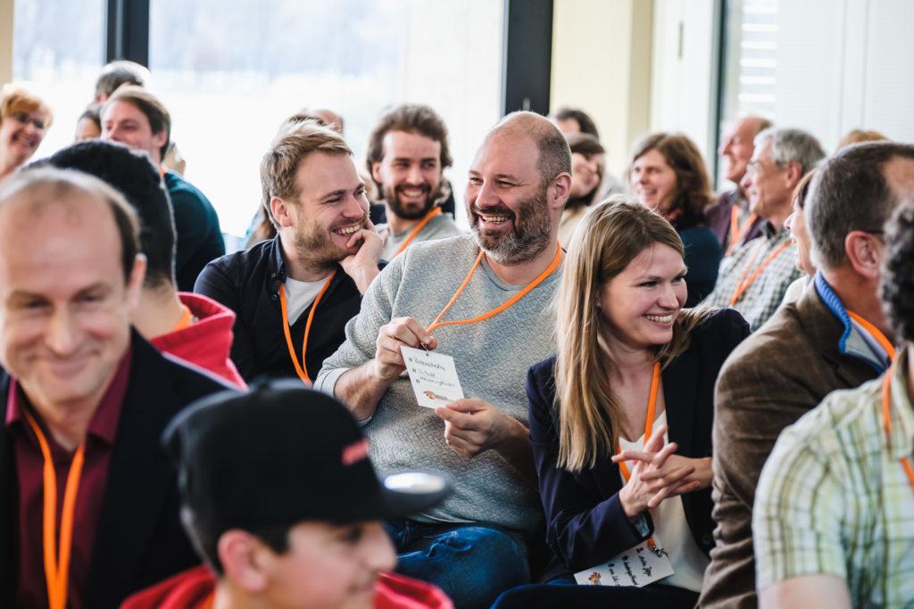Eine Gruppe von Menschen sitzt im Publikum einer Veranstaltung. Die Personen lachen und schauen nach links.