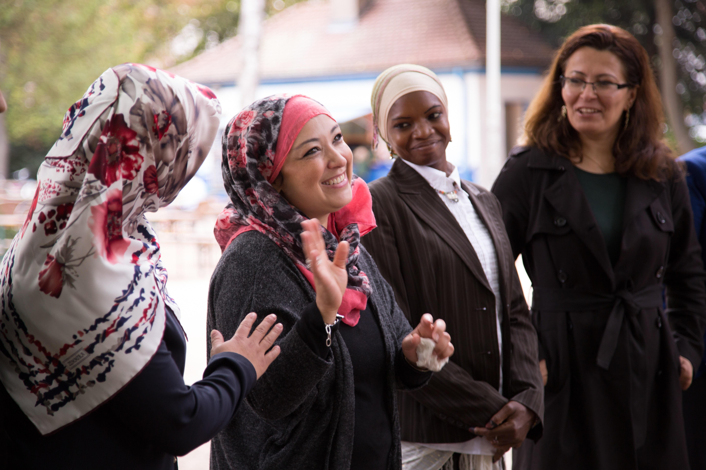 Mehrere Frauen mit Kopftuch und eine ohne stehen in einer Reihe und lachen.