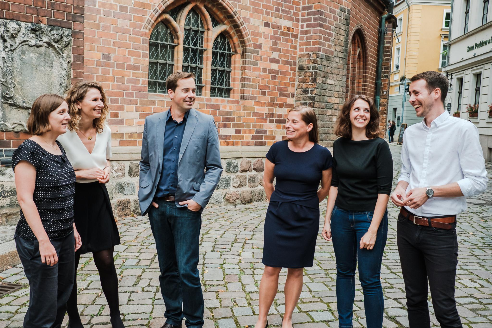 Vier Frauen und zwei Männer stehen vor einer Kirche in Berlin. Das ist das Team von openTransfer.