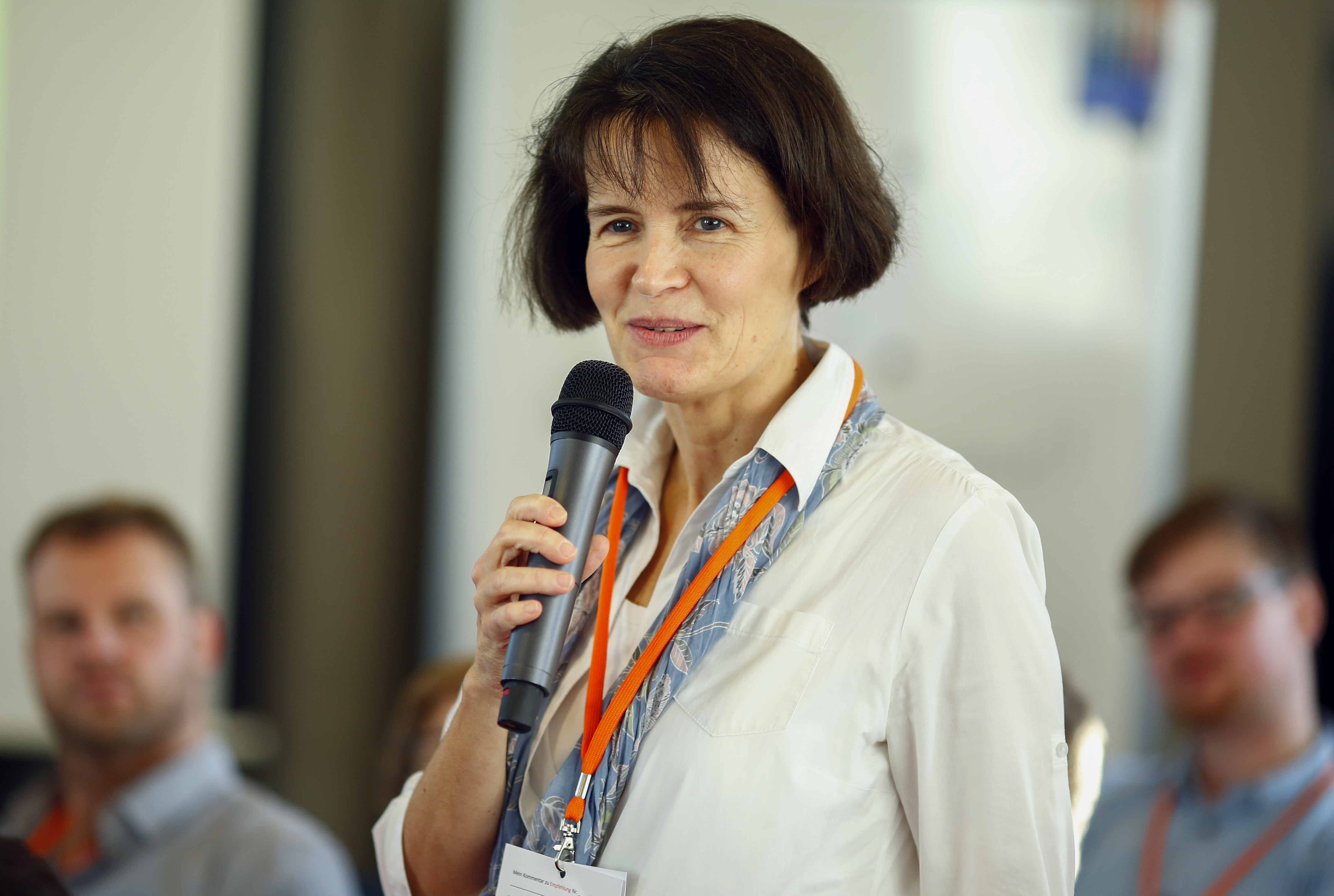 Eine Frau hält ein Mikro in der Hand und spricht vor mehreren Menschen.