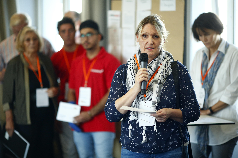 Eine Frau mit Mikrofon spricht vor einer Gruppe von Menschen.