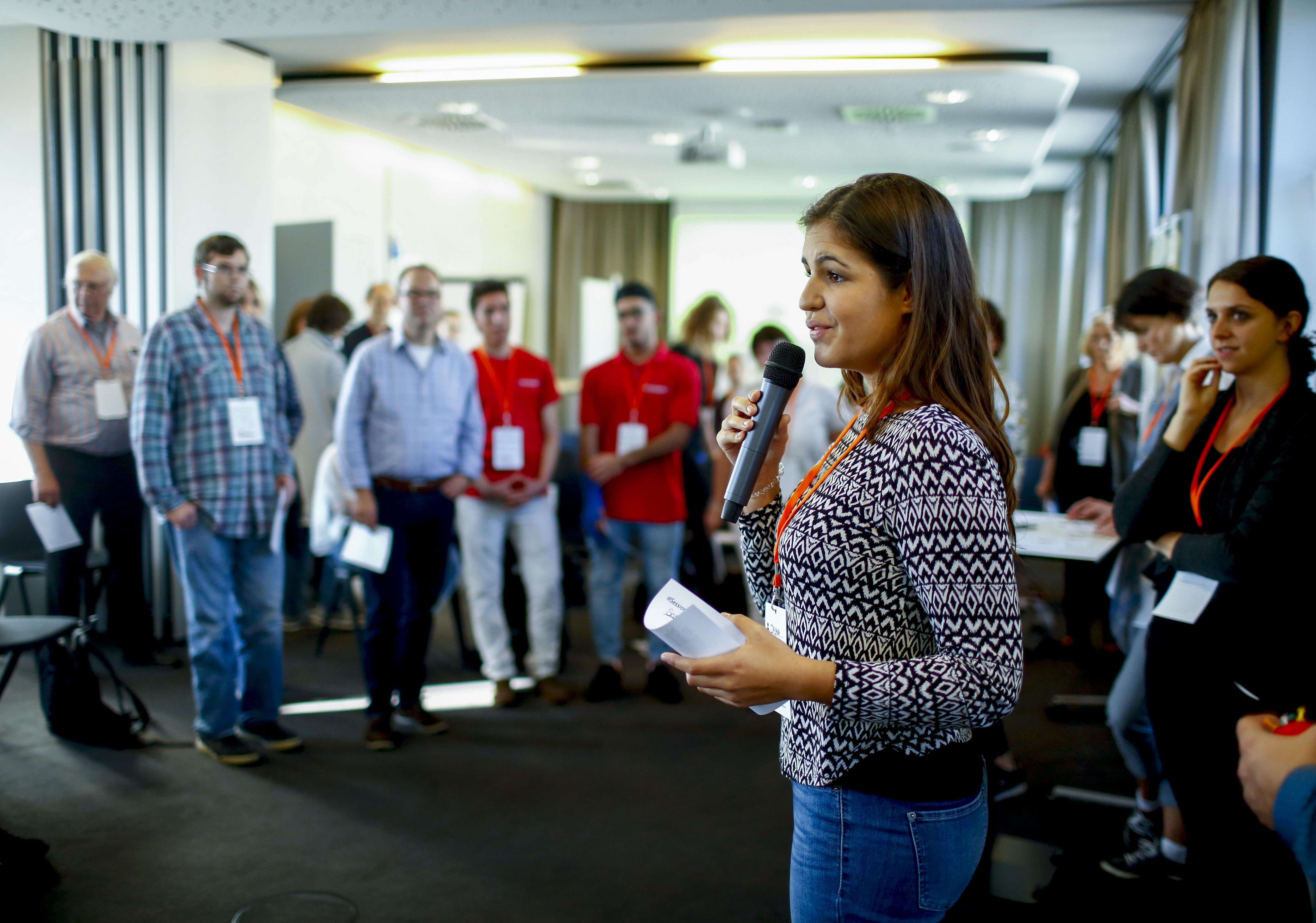 Eine junge Frau spricht vor einer Gruppe Menschen.