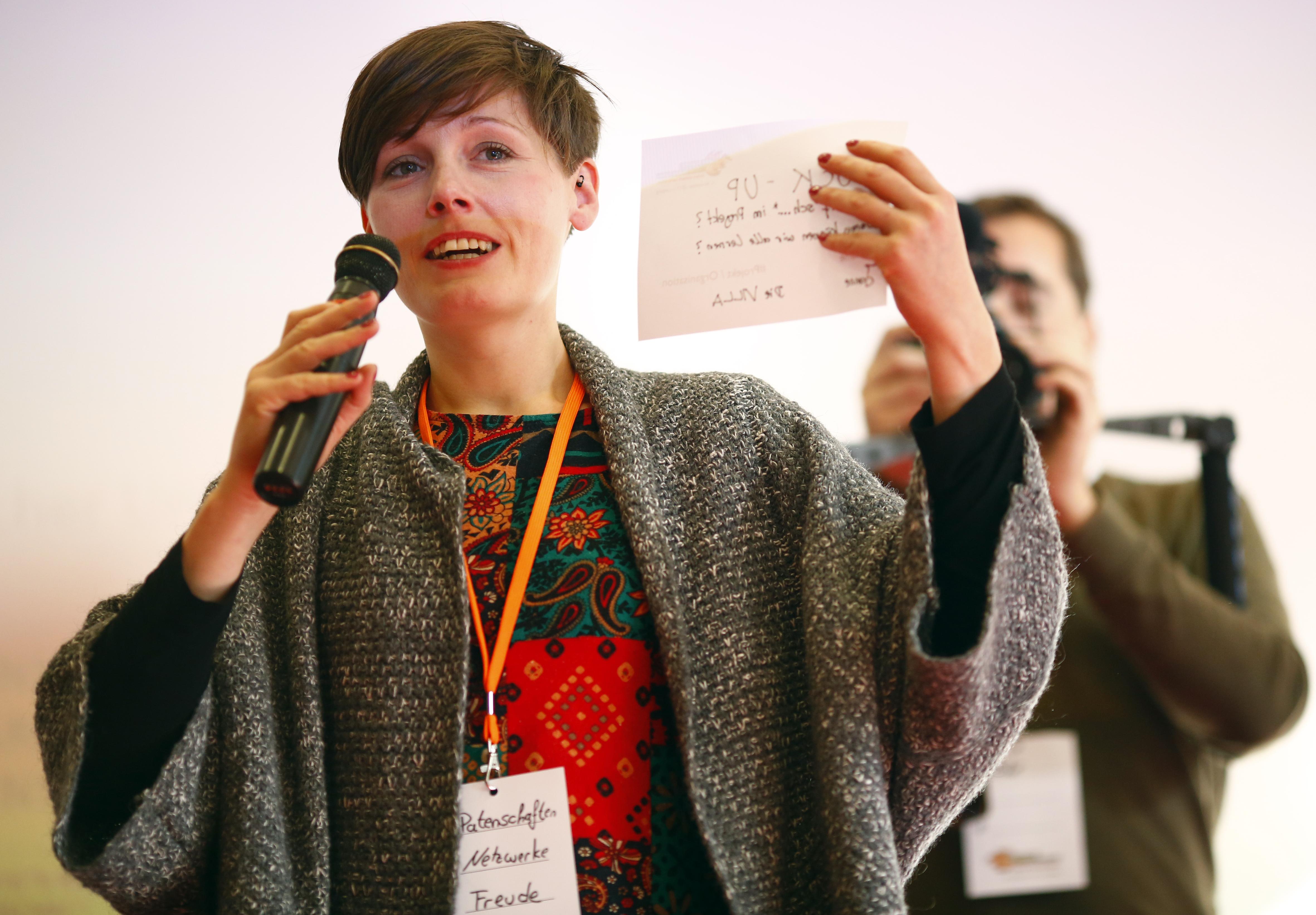 Eine junge Frau spricht in ein Mikro und gestikuliert.