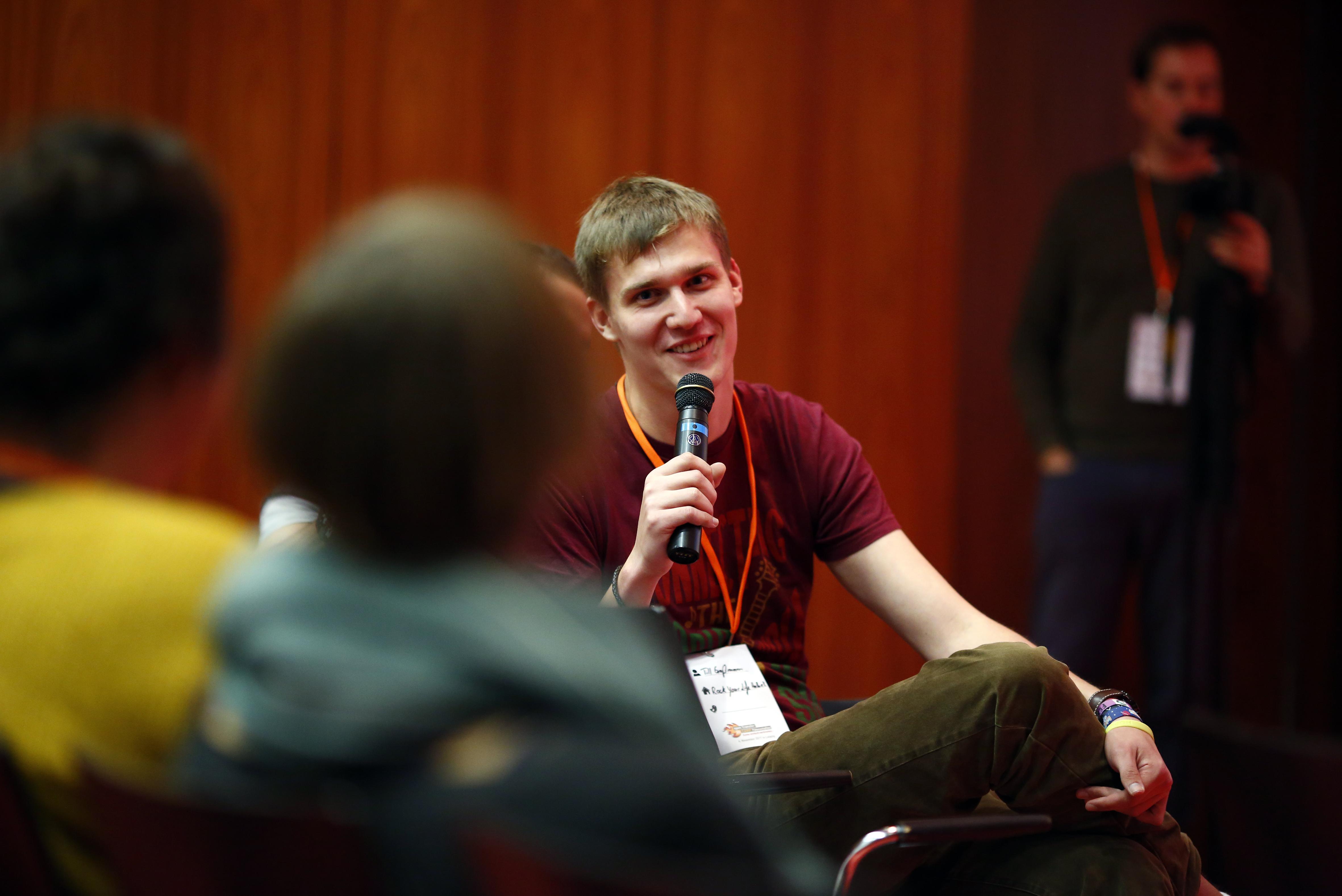 Ein junger Mann sitzt auf einem Stuhl und hält ein Mikro, im Vordergrund sind weitere Personen.