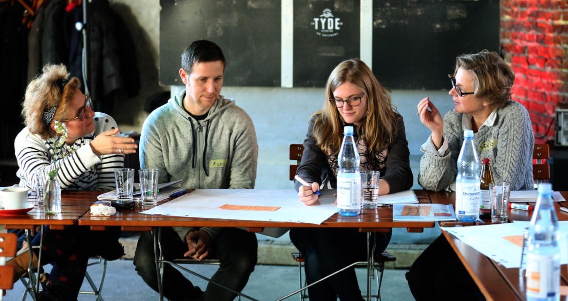 Drei Frauen und ein Mann sitzen um einen Holztisch und diskutieren angeregt.