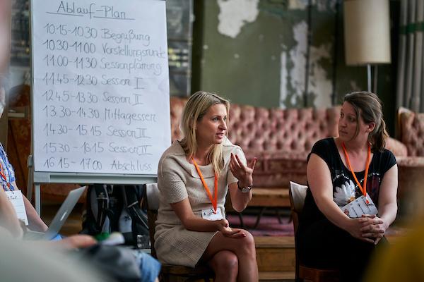 Zwei Frauen sitzen vor einer Flipchart und sprechen.