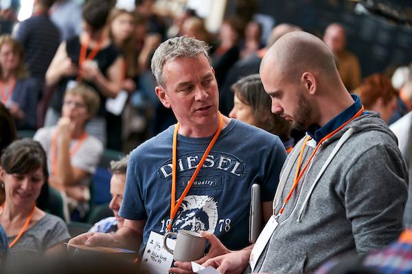 Zwei Männer unterhalten sich, im Hintergrund eine größere Menschenmenge.