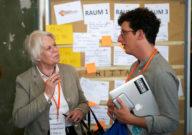 Ein junger Mann spricht mit einer älteren Frau.