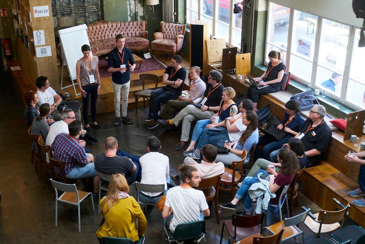 Eine Menschengruppe sitze im Stuhlkreis, zwei Referenten sprechen.