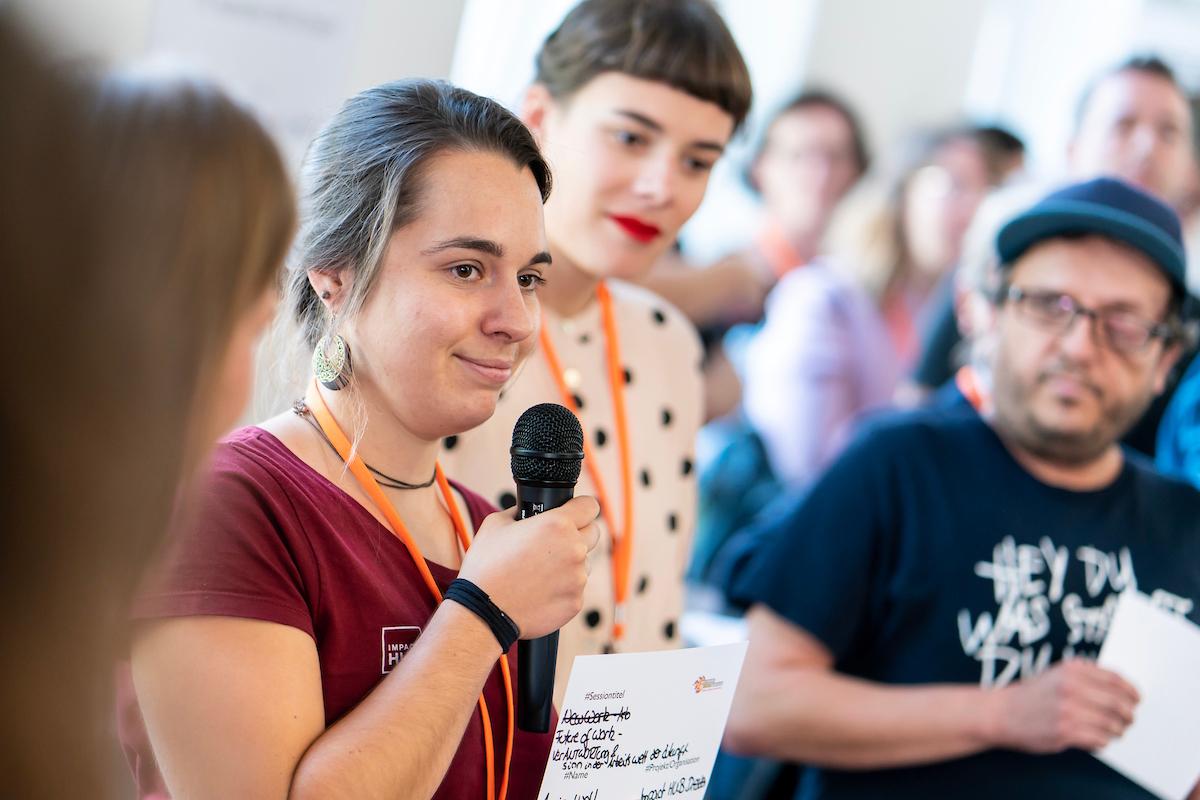 Ein Frau hält ein Mikrofon und ist von mehreren Menschen umgeben.