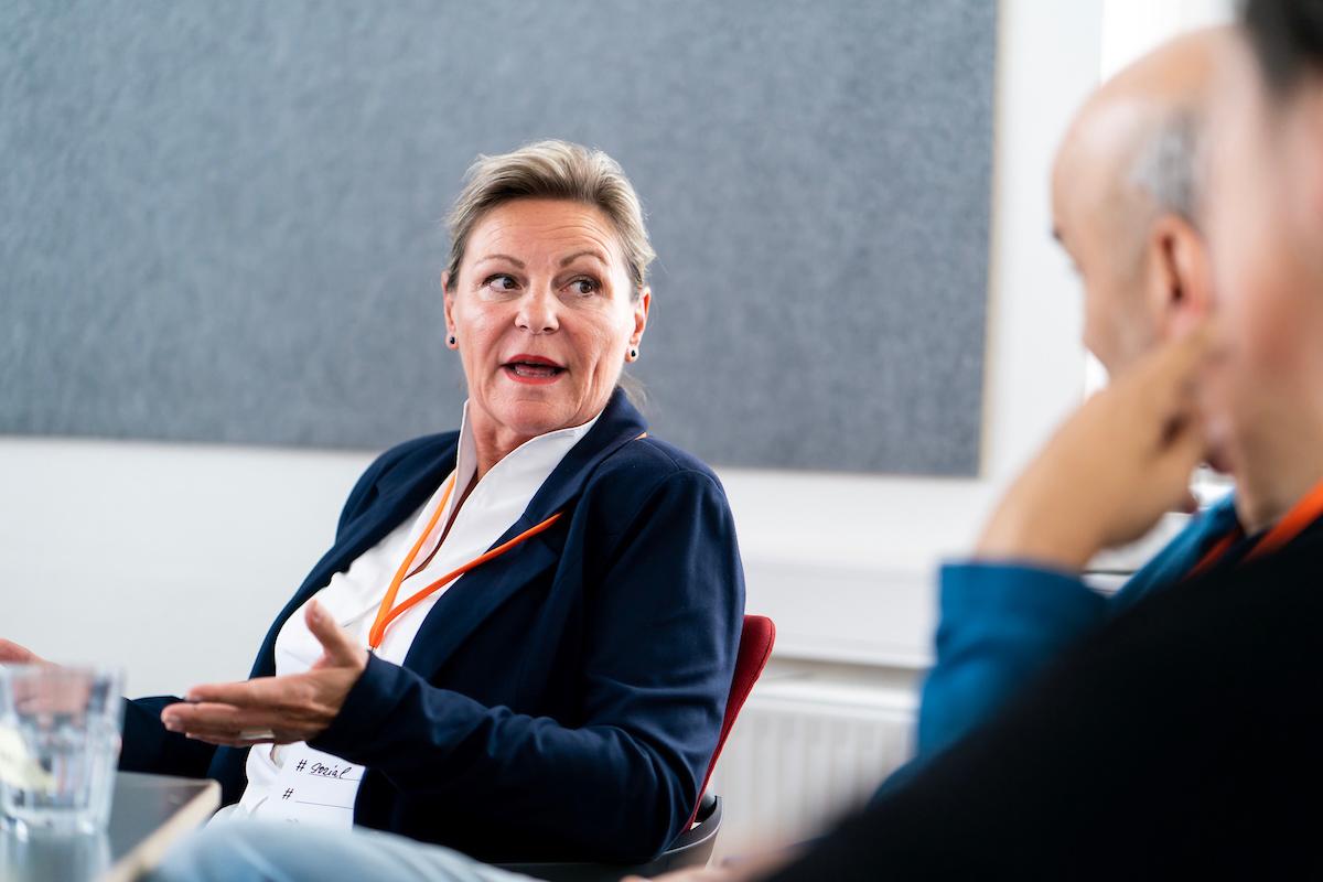 Eine Frau spricht zu einer Gruppe Menschen.
