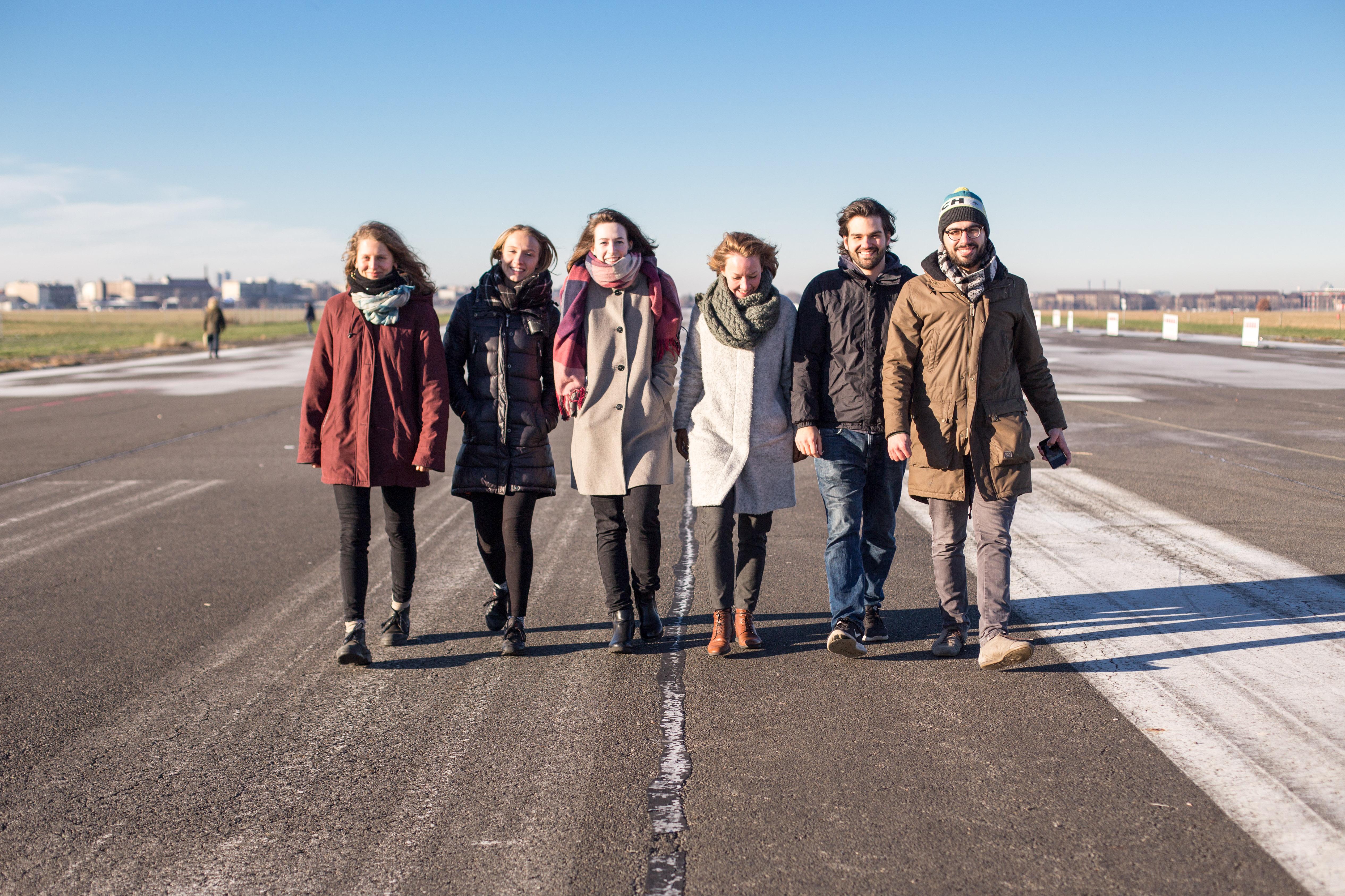 Eine Gruppe von sechs Leuten läuft auf der Start- und Landebahn des ehemaligen Flughafen Tempelhof in Berlin entlang.