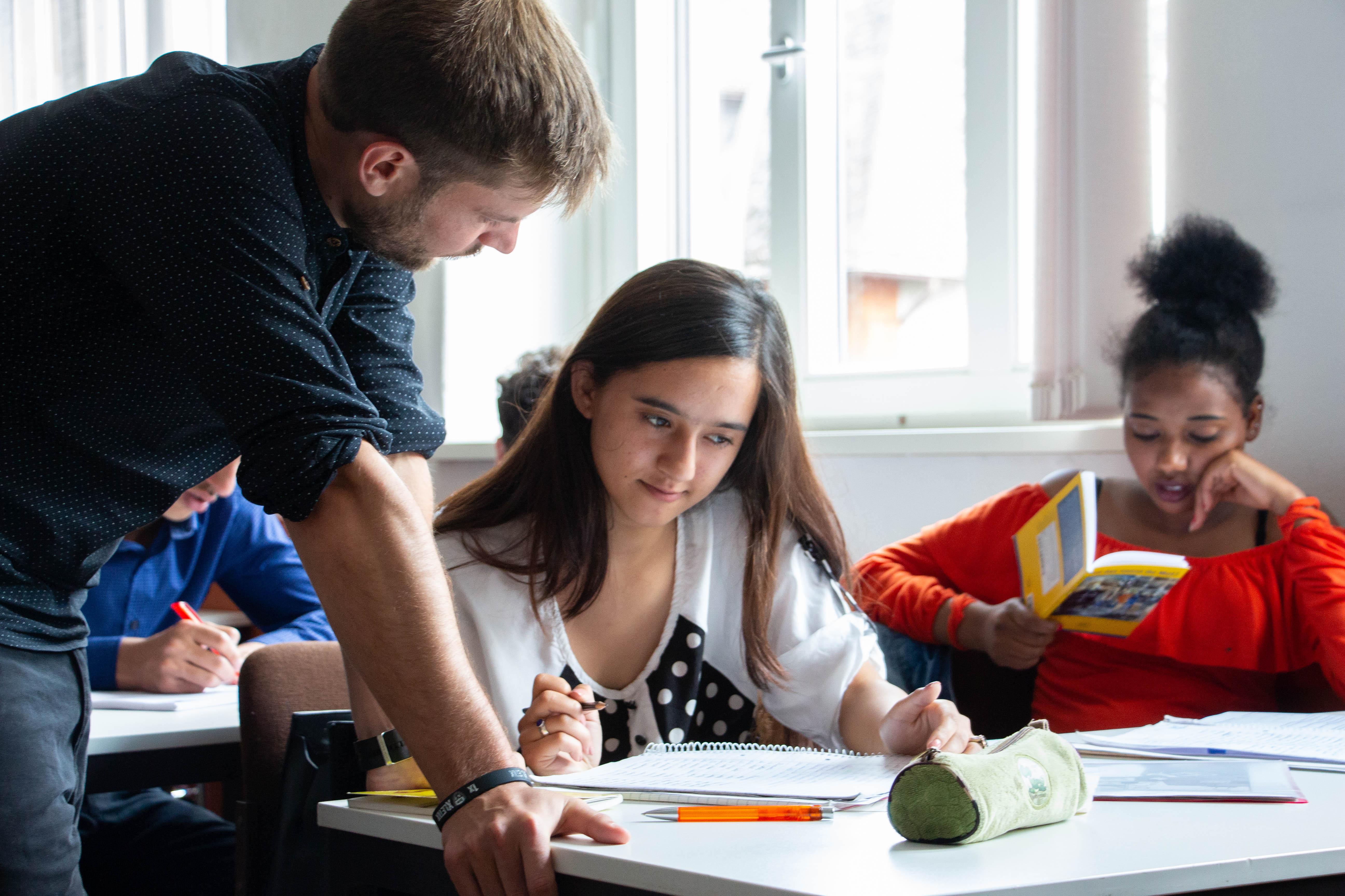 Zwei Schülerinnen sitzen an einem Tisch im Klassenraum. Eine Schülerin liest in einem Buch. Der Lehrer stützt sich auf dem Tisch ab. Schülerin und Lehrer schauen beide auf ein Papier.