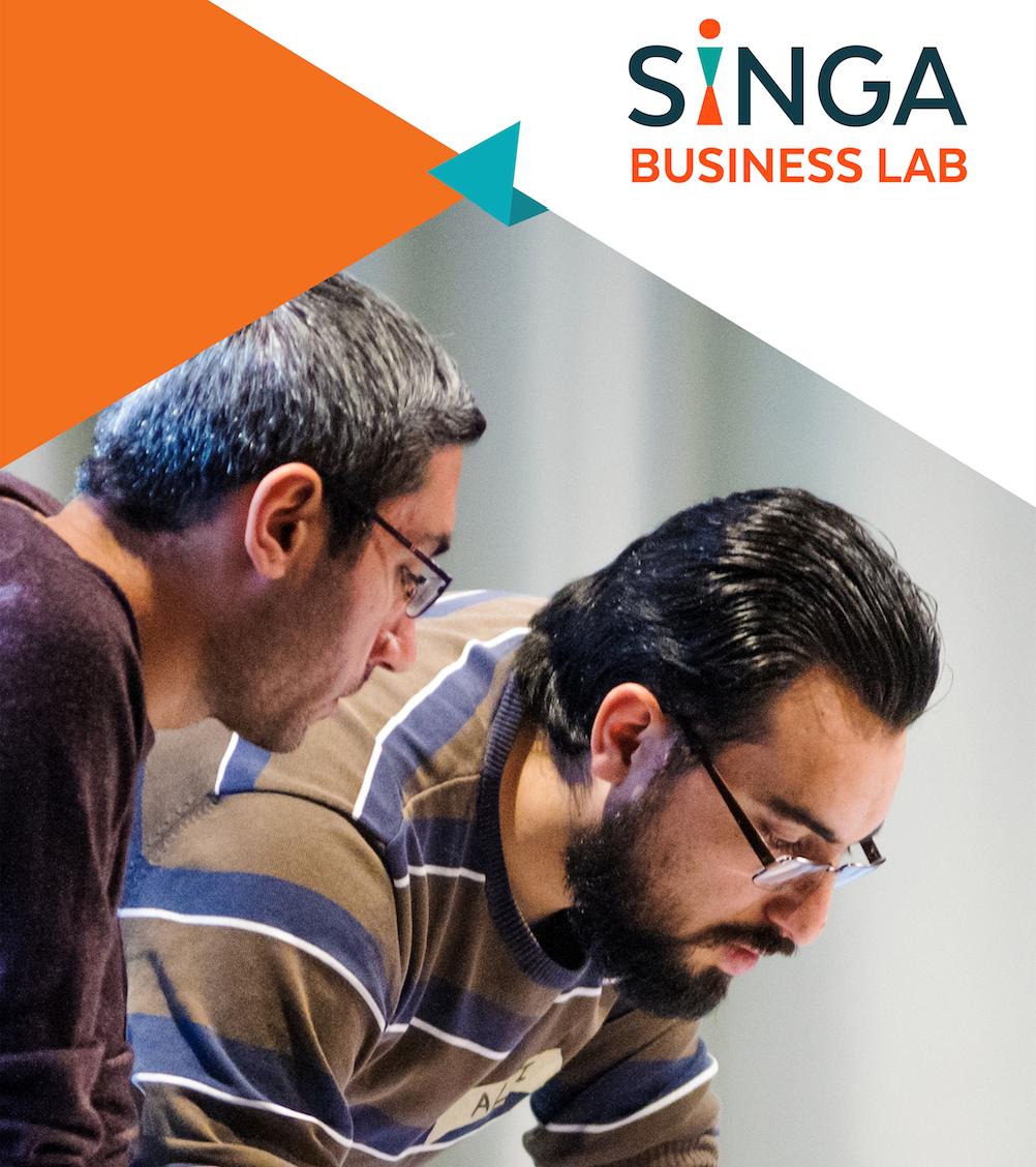 Zwei Männer beugen sich über etwas. Oben rechts im Bild ist das Logo des SINGA Business Lab zusehen.
