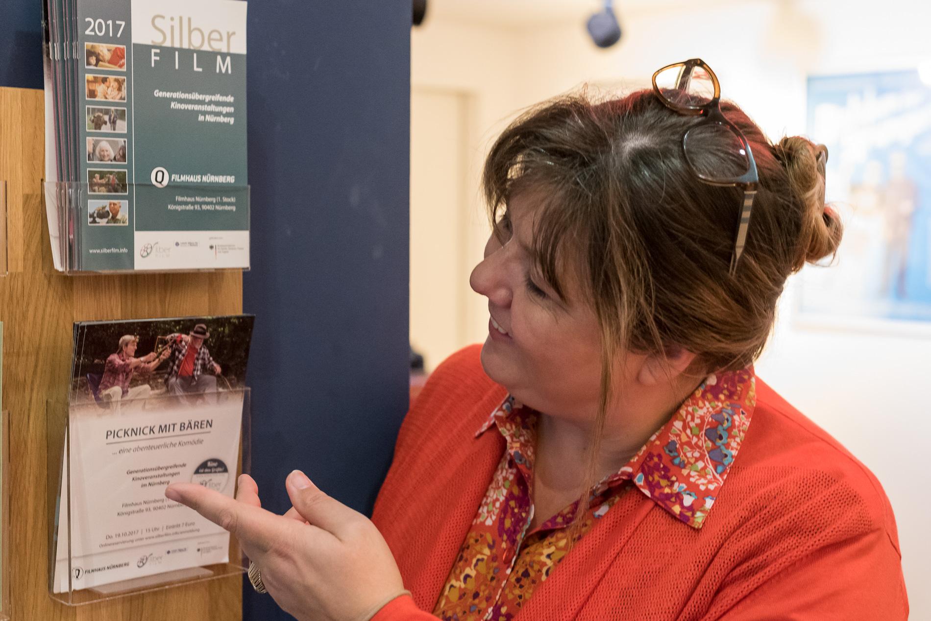 Eine Frau steht vor zwei Halterungen für Broschüren und zeigt mit der linken Hand auf eine der Broschüren.