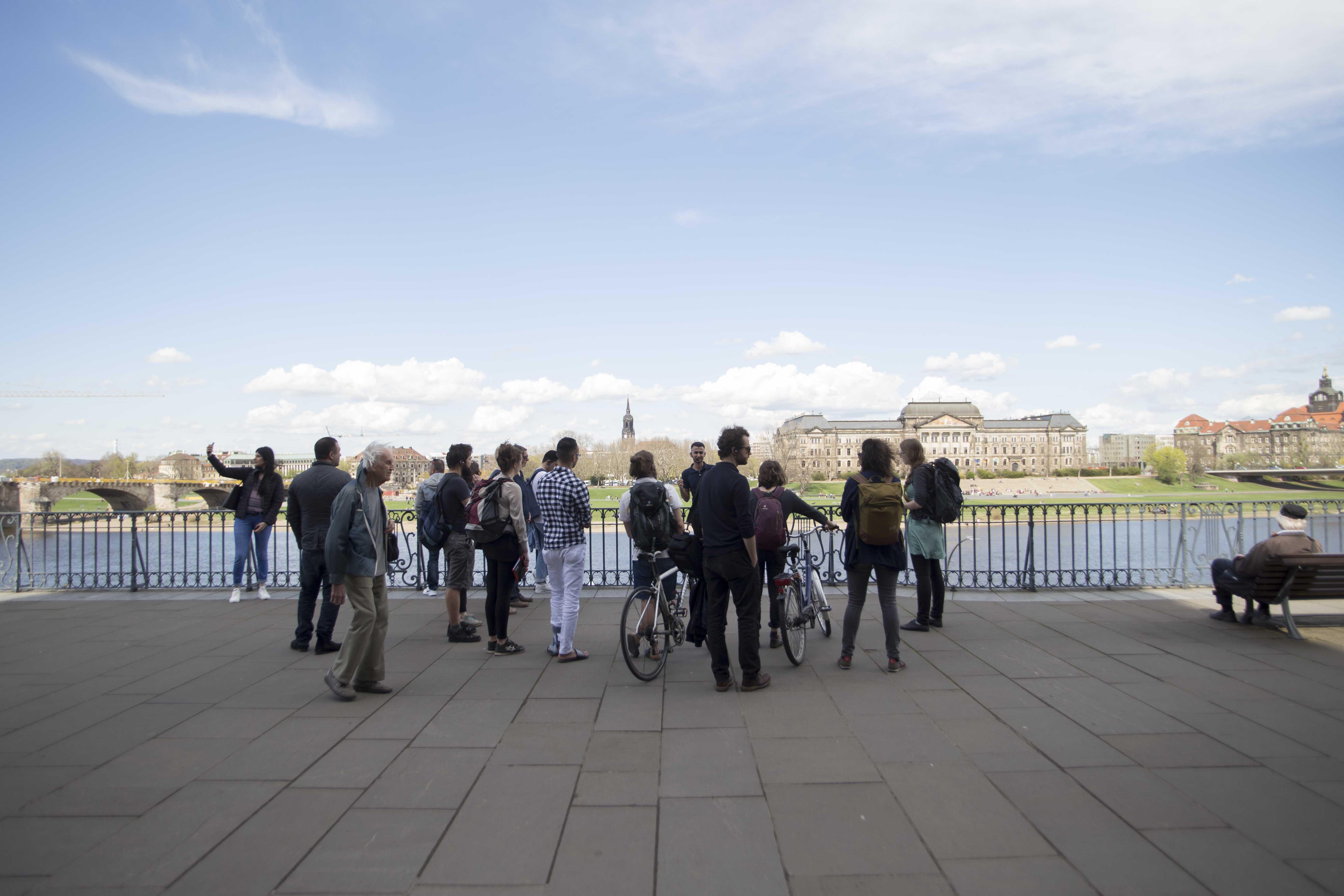 Eine Gruppe von Menschen steht um einen Stadtführer herum am Ufer eines Flusses.