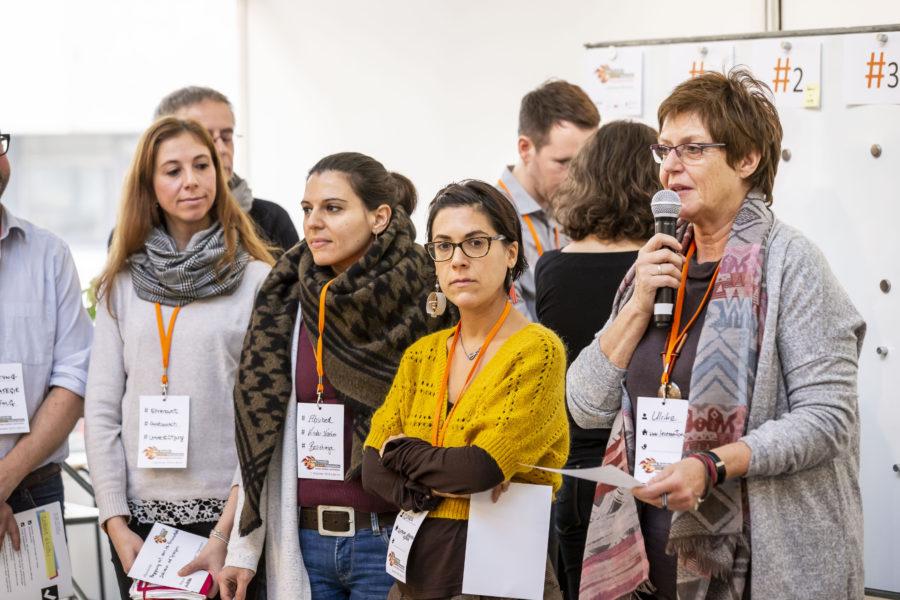 Eine Frau spricht in ein Mikrofon, mehrere Frauen stehen neben ihr.