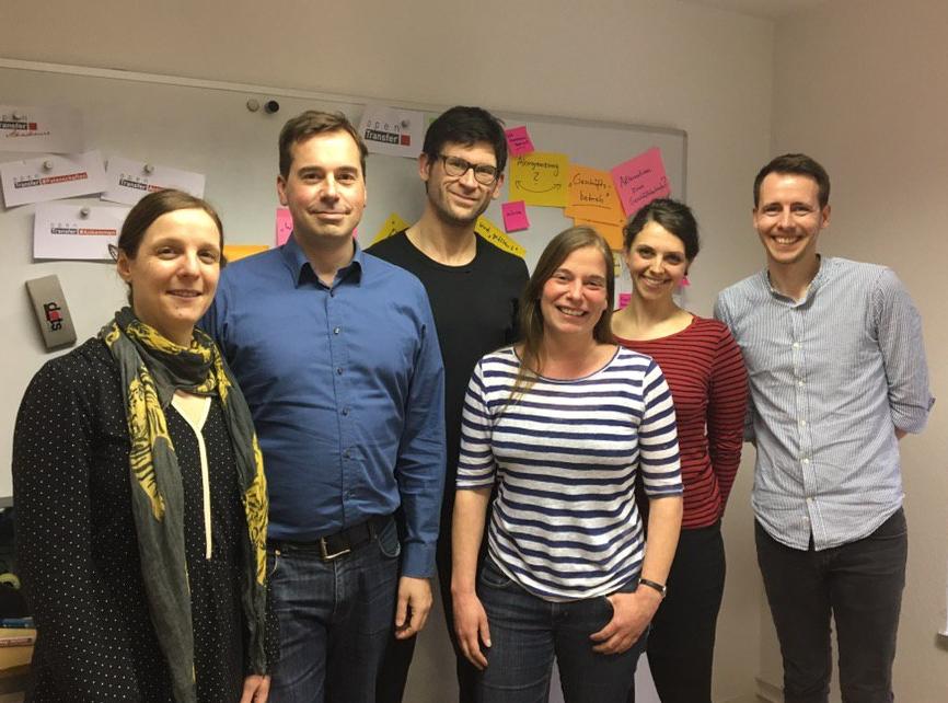 Teammitglieder der Stiftung Bürgermut stehen vor einem Wandboard mit Post-its
