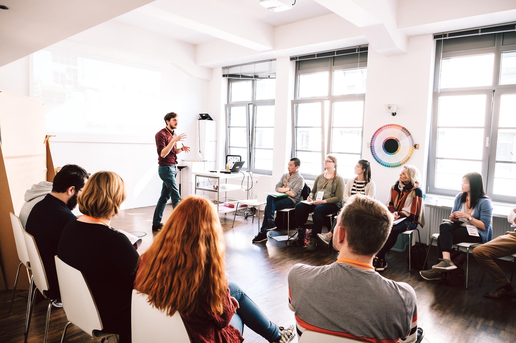 Ein Mann spricht vor einer Gruppe Menschen, die vor ihm im Stuhlkreis sitzt.