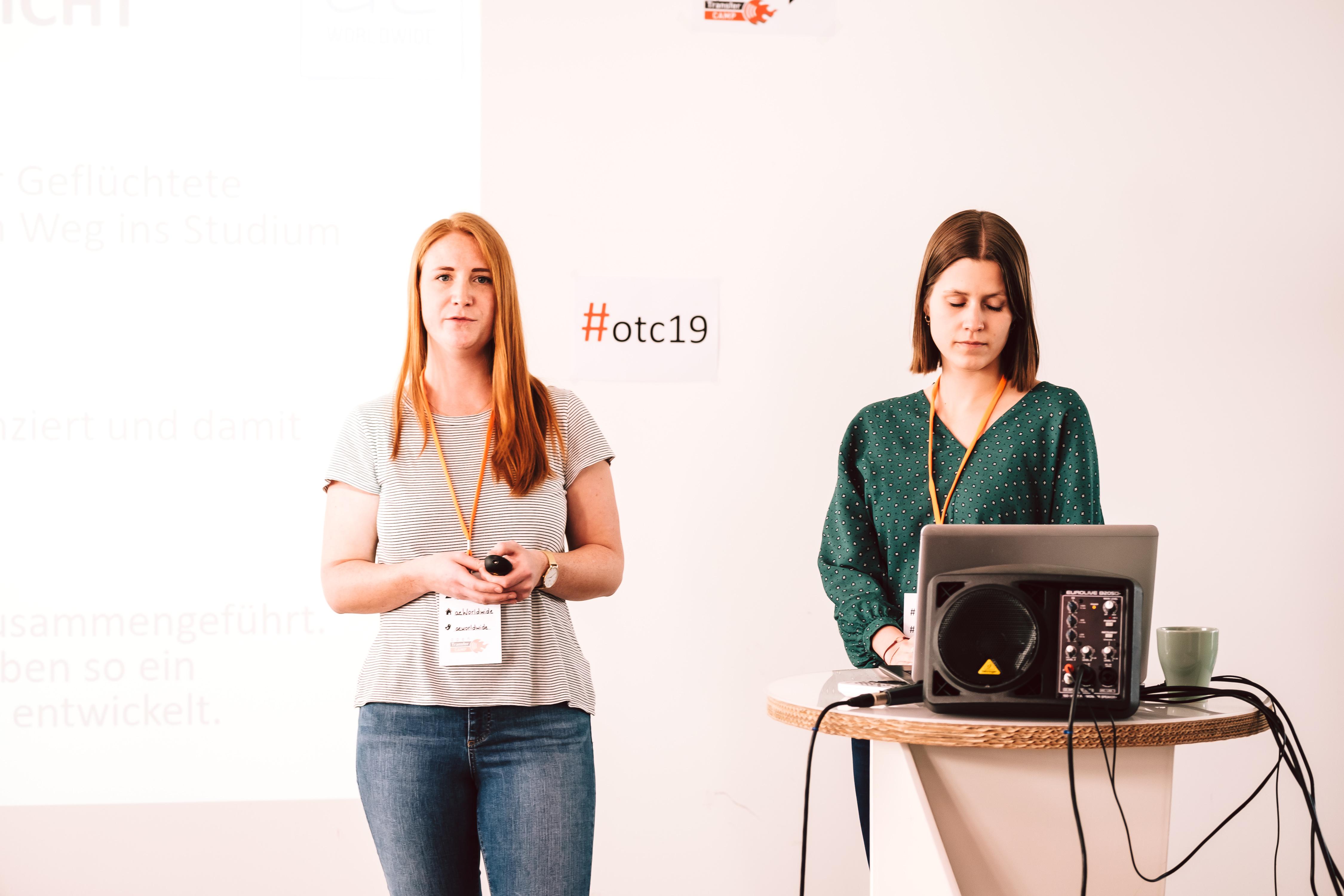 Zwei Frauen stehen vor einer weißen Wand mit dem hashtag #otc19.