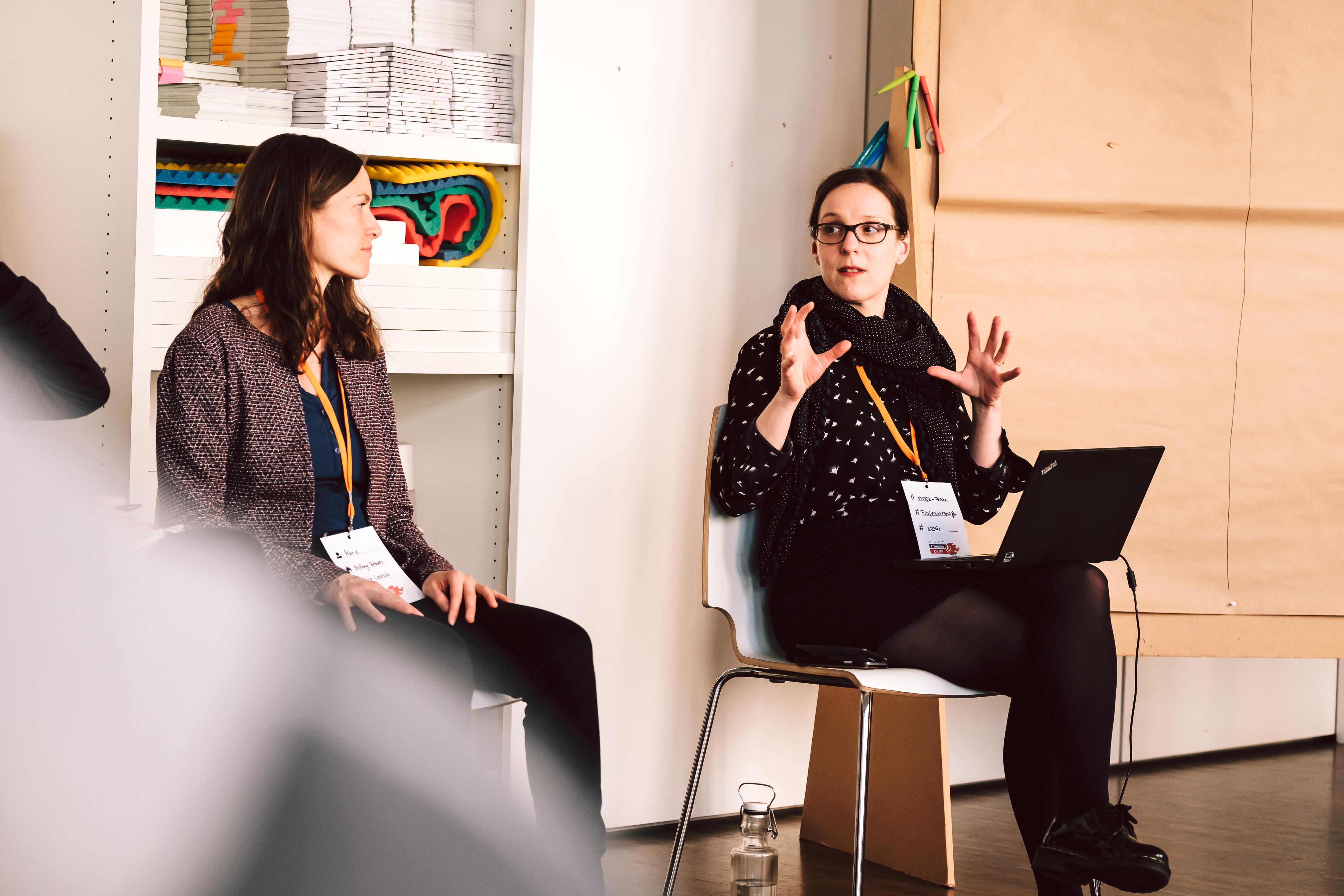 Zwei Frauen sitzen auf Stühlen, eine spricht und gestikuliert mit den Händen.