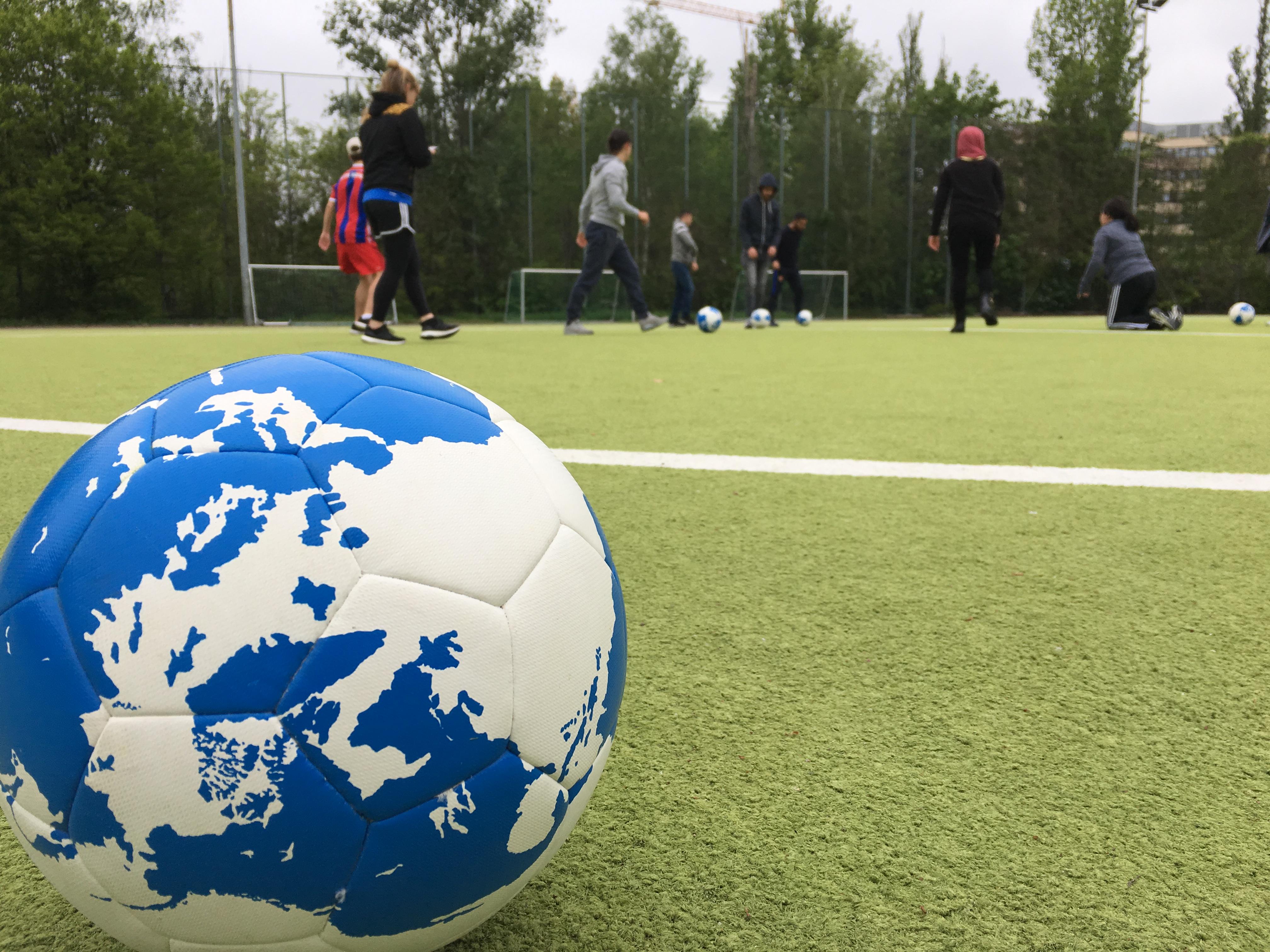 Ein Fußball, der als Erdball gestaltet ist, liegt auf einem Rasen, im Hintergrund spielen Jugendliche mit Bällen.