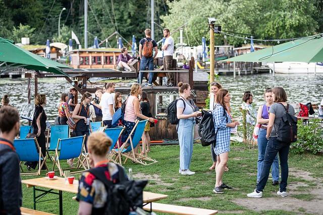 Menschen unterhalten sich auf einer Wiese, im Hintergrund Wasser und ein bebautes Floß.