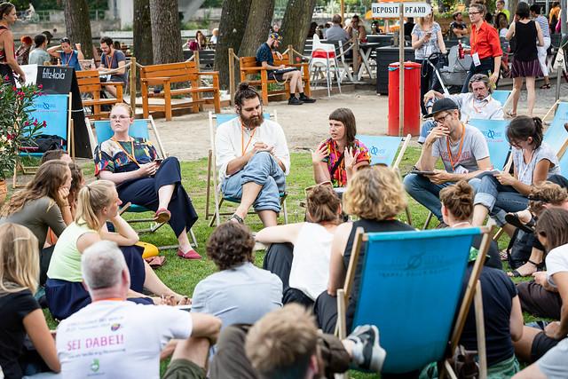 Eine Gruppe Menschen sitzen auf einer Wiese in Liegestühlen.