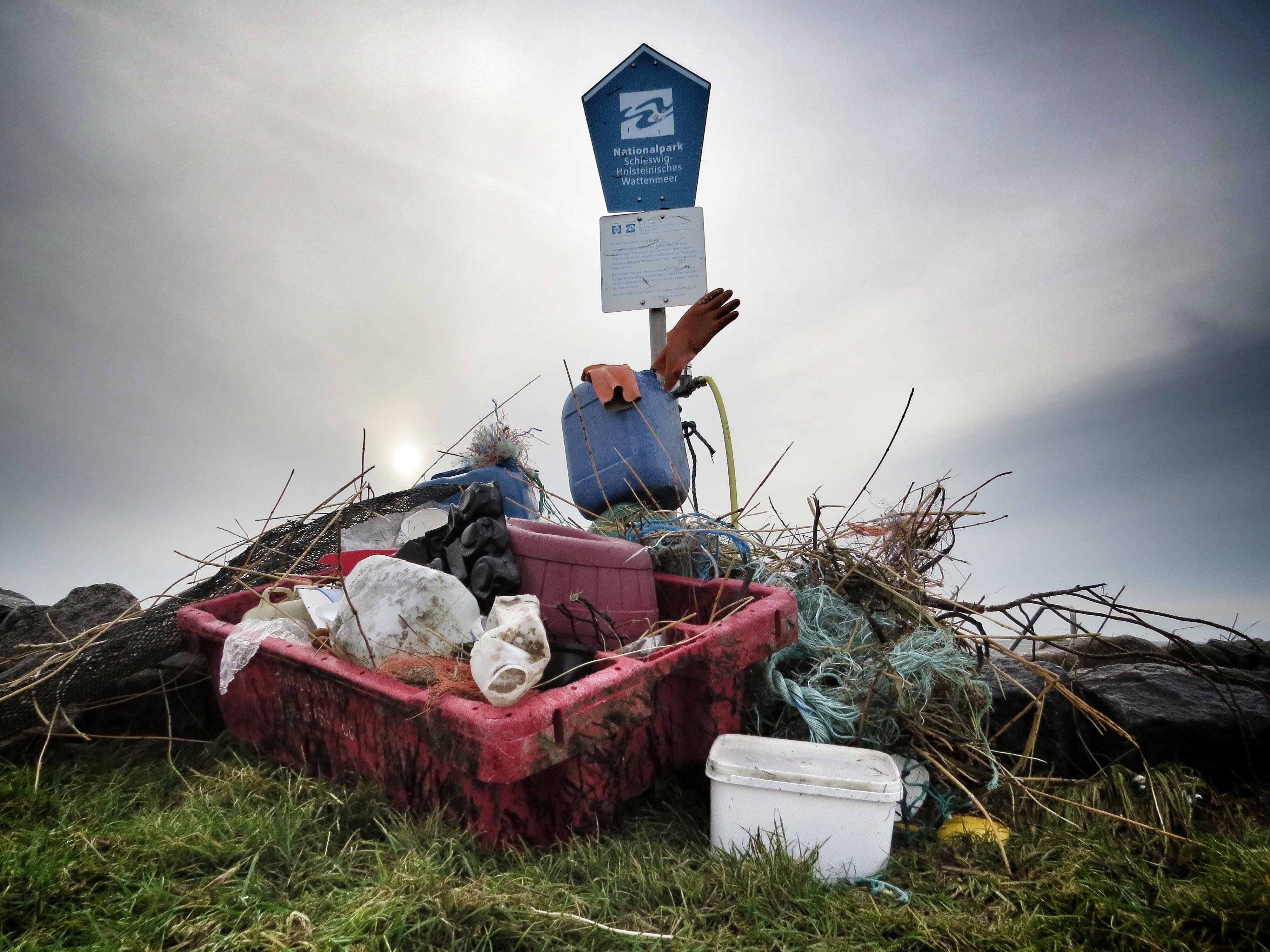 Vor einem Schild des Nationalparks Wattenmeer türmt sich Müll auf.