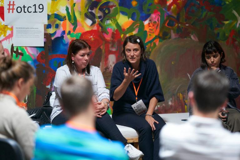 Eine Frau sitzt vor einer Wand mit Grafittis und erklärte einem Stuhlkreis etwas.