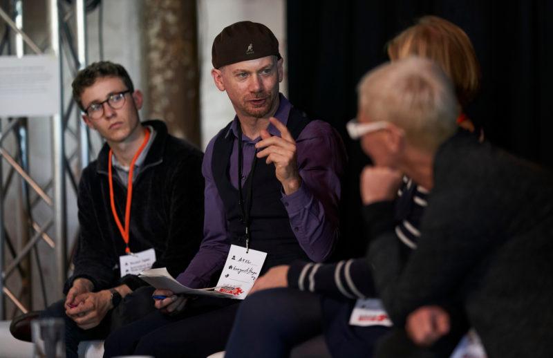 Ein Mann sitzt zwischen drei Zuhörerinnen.